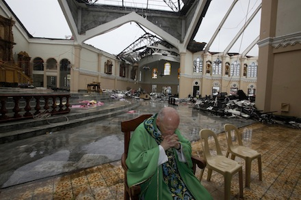Cardinal Theodore McCarrick, retired archbishop of Washington, prays in the ruined Cathedral of the Transfiguration of Our Lord in Palo earlier this month Below: More devastation wrought by Super Typhoon Haiyan (CNS)