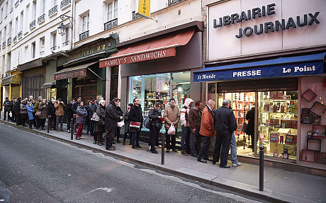 People wait outside a newsagents in Paris as the latest edition of French satirical magazine Charlie Hebdo goes on sale