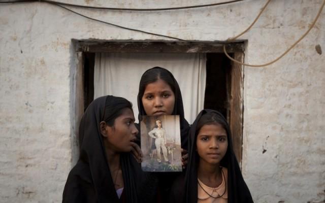 The daughters of Pakistani Christian woman Asia Bibi hold a photo of their mother (CNS)