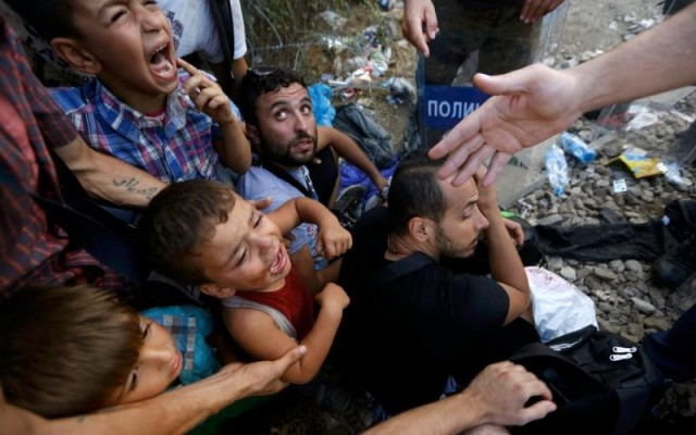 Syrian refugee children scream as they sit in front of Macedonian riot police at the Greek-Macedonian border