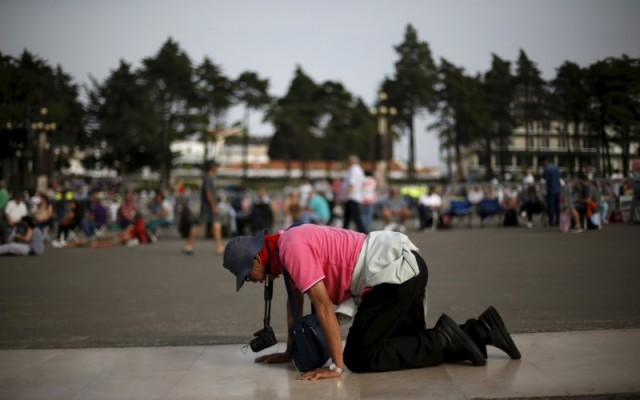 A pilgrim walks on her knees at the Marian shrine of Fatima in central Portugal