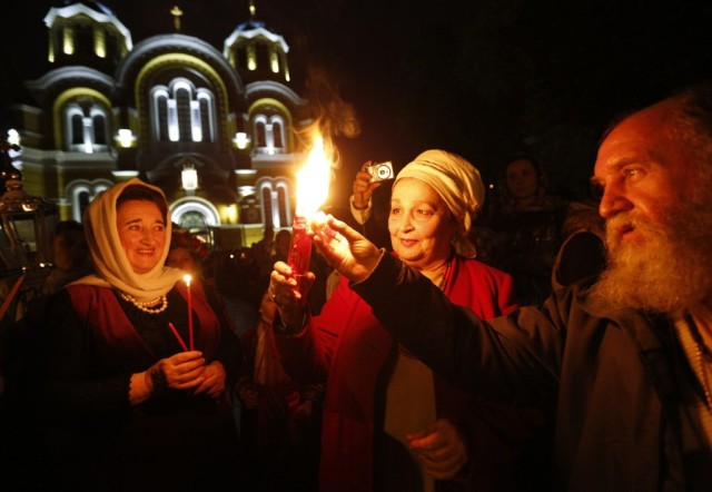 Ukrainian Orthodox believers light candles from the Holy Fire (AP)