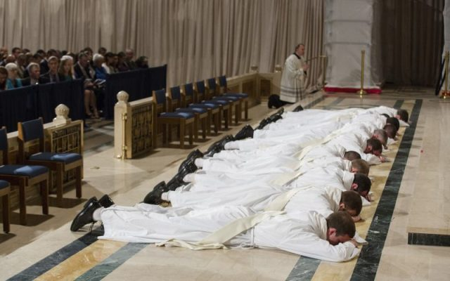 Eleven men lie prostrate during their ordination as priests (CNS photo/Jaclyn Lippelmann, Catholic Standard)