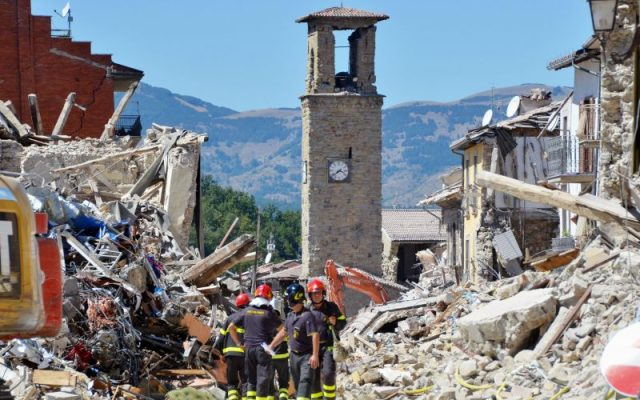 Firefighters clear rubble in front of the bell tower in Amatrice (AP)