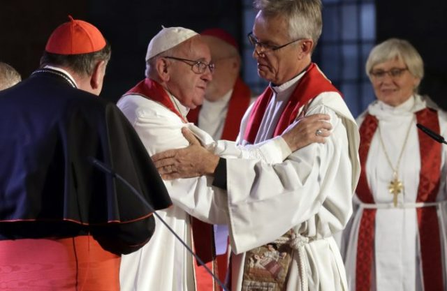 Pope Francis hugs Rev. Martin Junge, General Secretary of the Lutheran World Federation, as Lutheran Archbishop Ante Jackelen, Primate of the Church of Sweden, is seen in the background at right, during an ecumenical prayer at Lund's Lutheran Cathedral, in Sweden, Monday, Oct. 31, 2016. (AP Photo/Andrew Medichini)